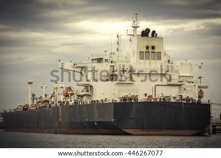 Huge tanker moored at oil terminal, ship is busy with cargo operations. Vintage effect added to the photo. - stock photo