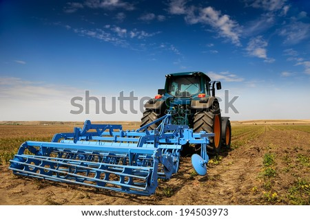 Huge tractor in the field - In a nice blue sunny day - stock photo
