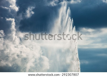 huge water fountain and airplane  against blue sky with white clouds - stock photo