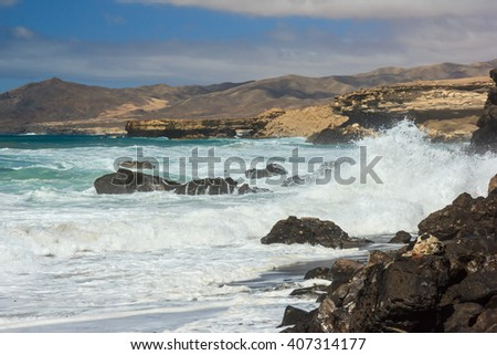 Huge waves crashing on the rocks on beach in La Pared, Fuerteventura island, Spain. - stock photo