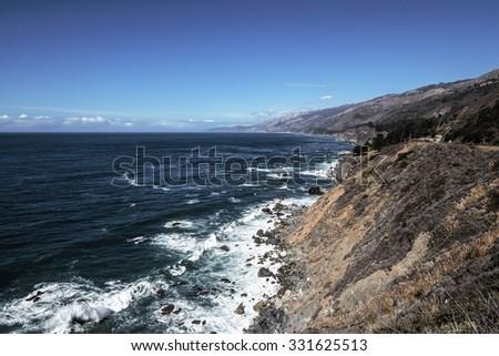 Huge waves splashing on huge rocks, off shore, along a rocky coastline, geological rock formations, traveling the Big Sur Highway (Highway 1), on the California Central Coast. - stock photo