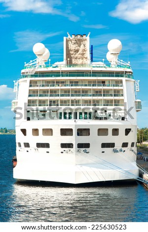 Huge white passenger cruise ship in port on a blue sky background. Outdoors - stock photo