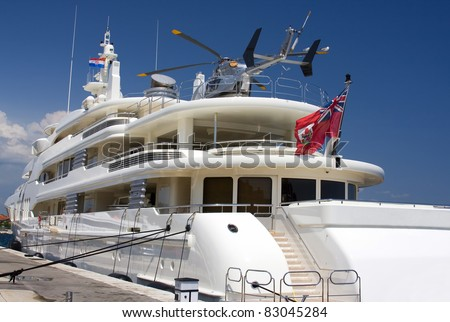 HUge white yacht with silver helicopter on deck. - stock photo