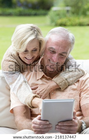 Hugging senior couple using digital tablet outdoors - stock photo