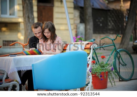 Hugging young couple in a summer cafe - stock photo