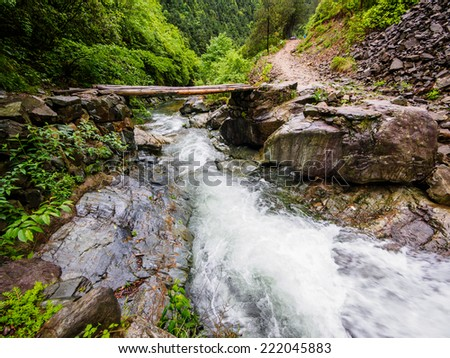 Huihang Ancient Trail Hiking Tour.  Image using slow shutter speed, simple bridge on river in mountains between Anhui and Zhejiang, China - stock photo