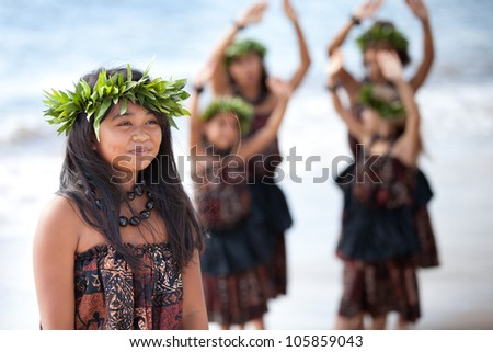 Hula girl on the beach with her fellow dancers behind her - stock photo