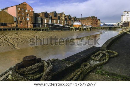 Hull, Humberside, UK. River Hull at low tide and an obsolete ship aground in the mud bank flanked by office and other buildings on one side and a barge anchored in the foreground, Hull, Yorkshire, UK. - stock photo
