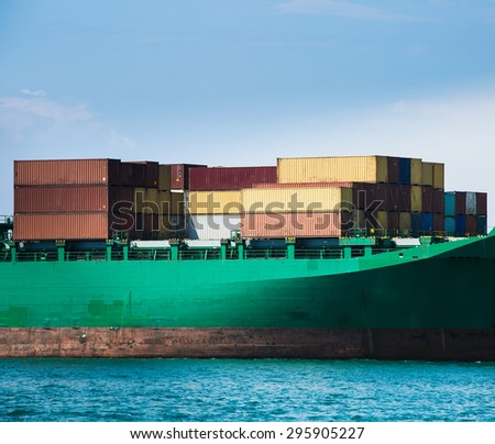 Hull of a big container ship docked in port, loaded with various colorful containers prepared for transportation. Global transportation, global business, consumerism concept and background.  - stock photo