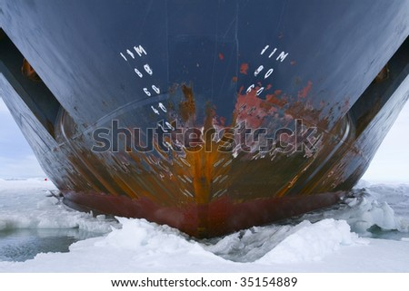 Hull of an icebreaker parked in the ice on Antarctica - stock photo