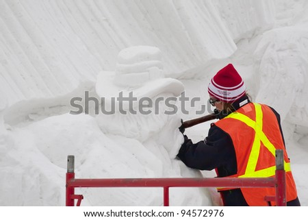 HULL, QUEBEC - FEBRUARY 3: Unidentified sculptor working at Jacques Cartier Park on one of the many giant snow sculptures of the Winterlude Festival, on opening day, February 3, 2012, Hull, Quebec. - stock photo