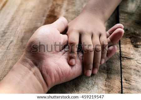 Human and a kid holding hands together on the wood table - stock photo