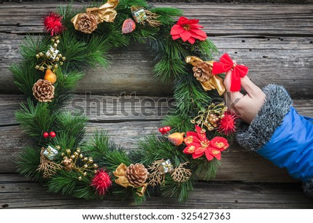 Human arm with decorative red bow and blue sleeve at log cabin wall with holiday Christmas wreath background - stock photo