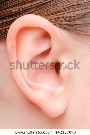 human ear image of a young woman close up - stock photo