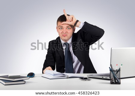 Human emotions, facial expressions, feelings, nature-young businessman showing loser sign on forehead, looking at you on gray background - stock photo