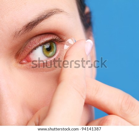 human eye with corrective lens on a blue background - stock photo