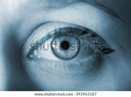 Human eye with reflection. Blue toned image. Macro shot. - stock photo