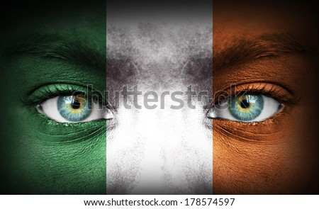 Human face painted with flag of Ireland - stock photo