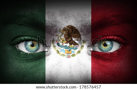 Human face painted with flag of Mexico - stock photo