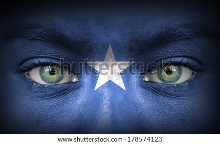 Human face painted with flag of Somalia - stock photo