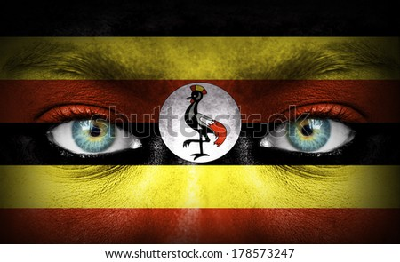 Human face painted with flag of Uganda - stock photo