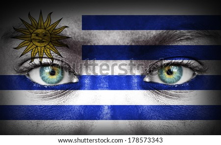 Human face painted with flag of Uruguay - stock photo