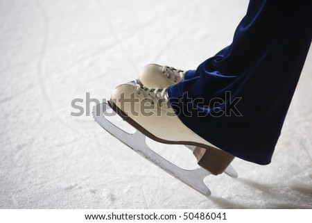 Human feet in fads standing on ice on the brink of an edge on skating rink - stock photo