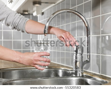 Human filling a glass of water - stock photo