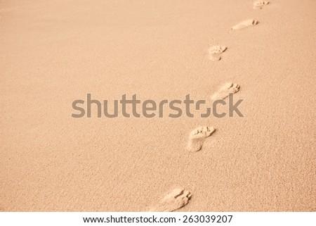 Human footprints on beach sand. Horizontal shot with copy space - stock photo