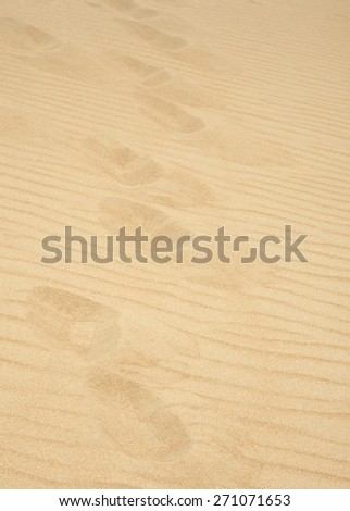 Human footsteps in dry dessert sand for background use - stock photo