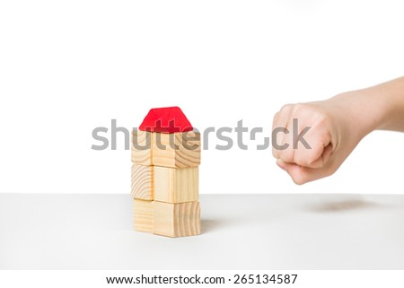 Human hand about to destroyi house made of wooden blocks - stock photo