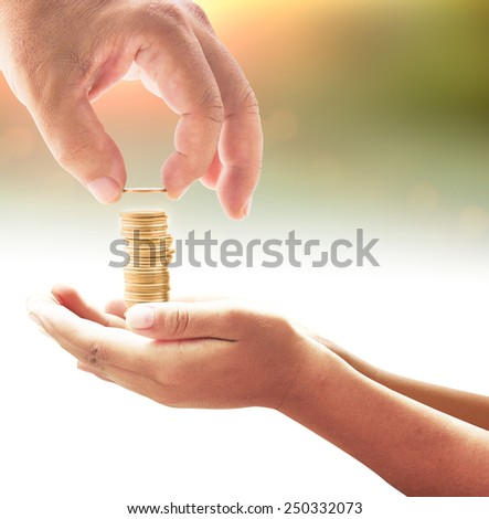 Human hand adding a golden coin in golden coins on another hands over blurred sunset background. Money coin concept. - stock photo