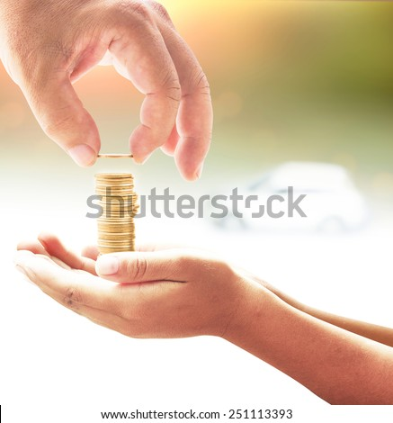 Human hand adding a golden coin in golden coins on another hands over white car on sunset background. Concept for money coin, insurance, buying, renting, repair, fuel , service. - stock photo