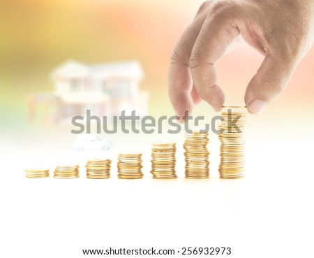 Human hand adding a golden coin in the final row of golden coins over blurred house and car on sunset background. Concept for money coin, buying, renting, service, Investment, Insurance Agent. - stock photo