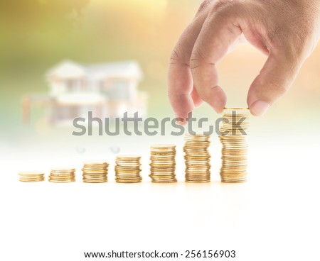 Human hand adding a golden coin in the final row of golden coins over blurred house on sunset background. Concept for money coin, insurance, buying, renting, service. - stock photo
