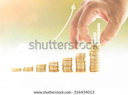 Human hand adding golden coin on stacks of coins over graph finance on blur white car background. Concept for money, insurance agent, buying, renting, repair, fuel, service, Happy New Year 2016. - stock photo