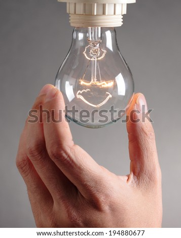 human hand changing a light bulb - stock photo