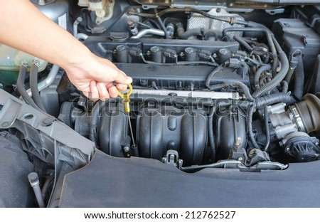 human hand checking engine oil of modern car - stock photo