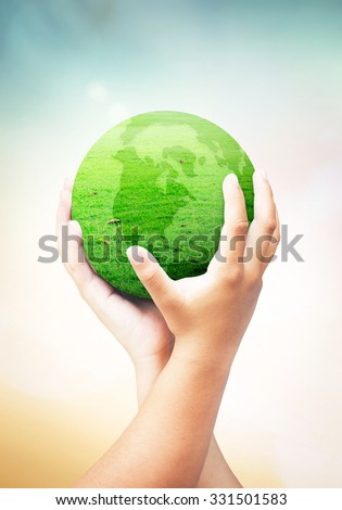 Human hand hold globe grass on beautiful nature background. Investment Saving Synergies Ecology World Environment Day CSR Mission Philosophy Go Green Work Trust Harmonious Cancer Spring ROI concept - stock photo
