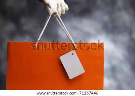 Human hand holding an orange bag. - stock photo