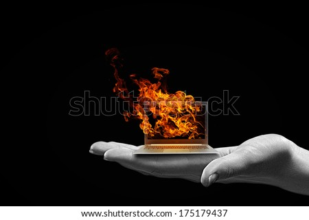 Human hand holding burning laptop on palm - stock photo