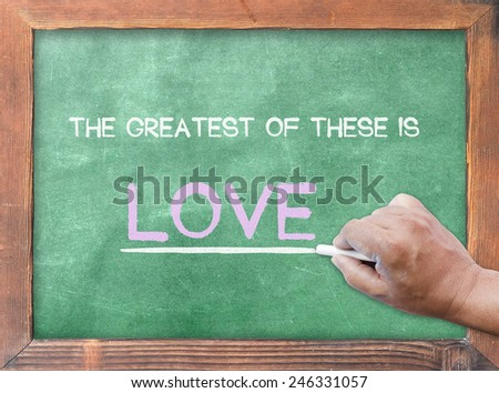 "Human hand holding chalk and writing text form bible ""the greatest of these is love"" on green board. - stock photo"