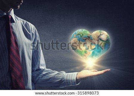 Human hand holding digital icon of planet earth. Elements of this image are furnished by NASA - stock photo