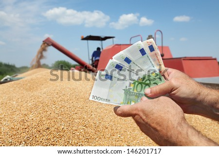 Human hand holding Euro banknote with wheat and combine in background - stock photo