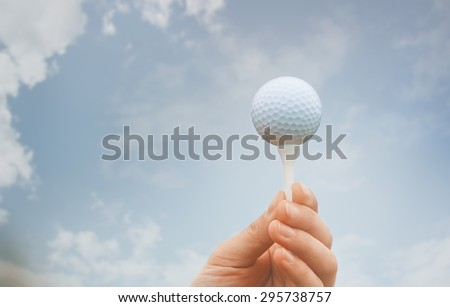 Human hand holding galf ball against the sky background - stock photo