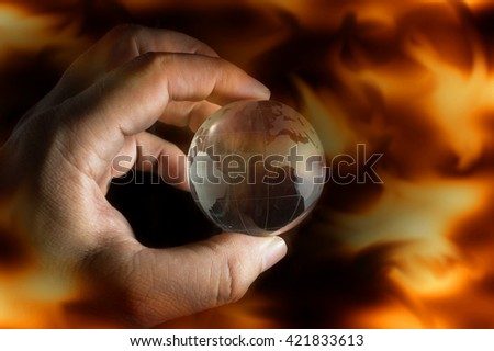 Human hand holding globe,fire flame screen. - stock photo