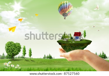 Human hand holding houses surrounded by nature - stock photo