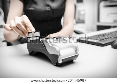 Human hand holding plastic card in payment - stock photo