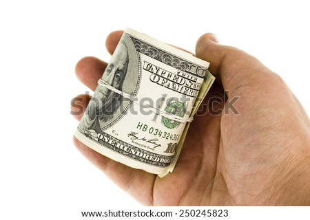 Human hand holding rolled up paper dollar currency - stock photo
