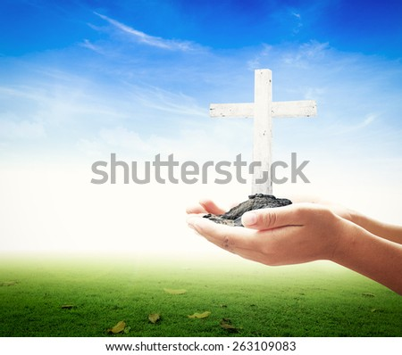 Human hand holding the wooden white cross over nature background. - stock photo
